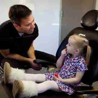 A dentist interacting with a young patient.